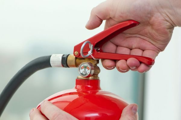 Person triggering a fire extinguisher